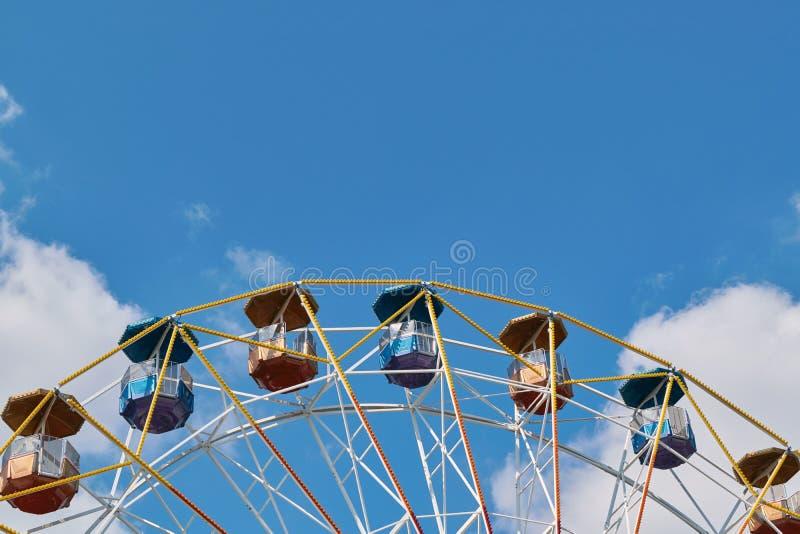 Ein großes Riesenrad an einem Vergnügungspark auf einem Hintergrund des blauen Himmels stockfotos