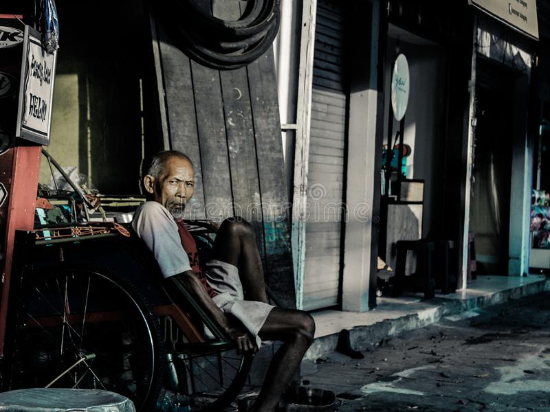 Ein Großvater, der beim Warten auf einen Passagier stillsteht stockfotografie