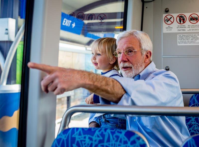 Ein Großvater verbringt Qualitäts-Zeit mit seinem Enkel auf einem Schienen-Zug stockfotos