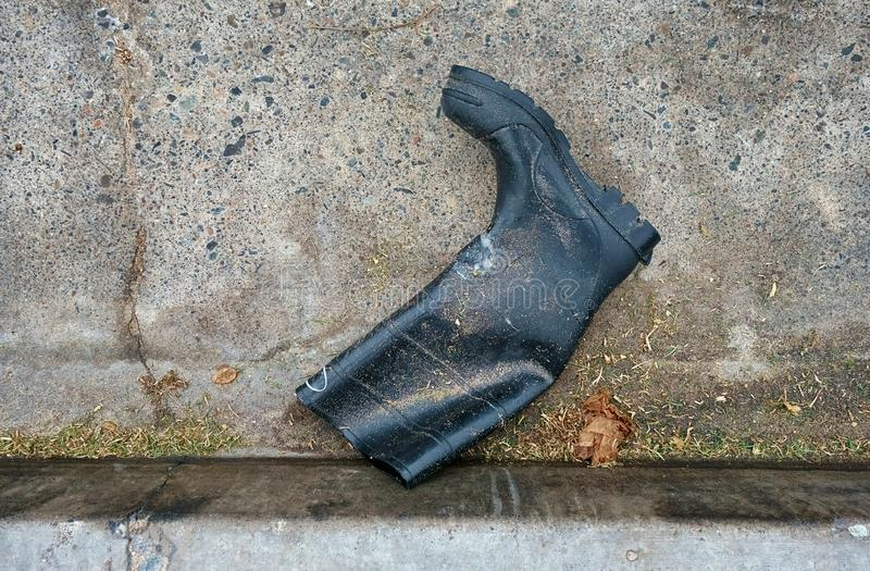Ein Gummiarbeitsstiefel, der in die Gosse einer Straße legt stockfotos