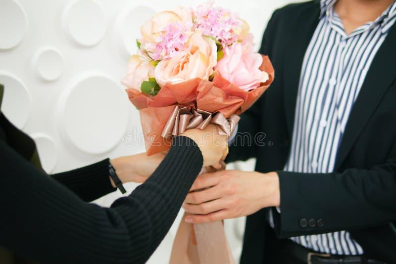 Ein gut aussehender Mann gibt einem schönen Mädchen im Büro Blumen stockfoto