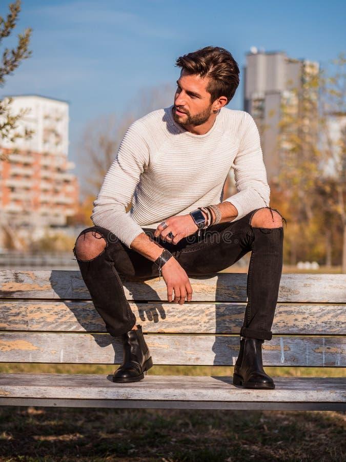 Ein gut aussehender Mann im Stadtpark, sitzend stockfoto