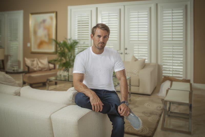 Ein gut aussehender Mann stellt auf den Arm der Couch kreuzte Beinblicke an der Kamera ein lizenzfreie stockfotografie