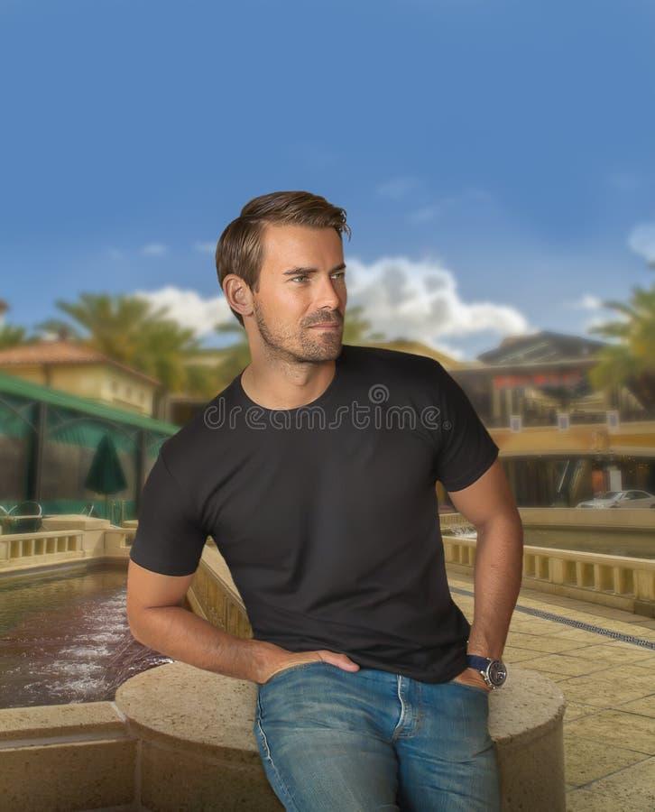 Ein gut aussehender Mann stellt am Ende eines Wasserbrunnens mit den Händen im Paket ein lizenzfreies stockbild