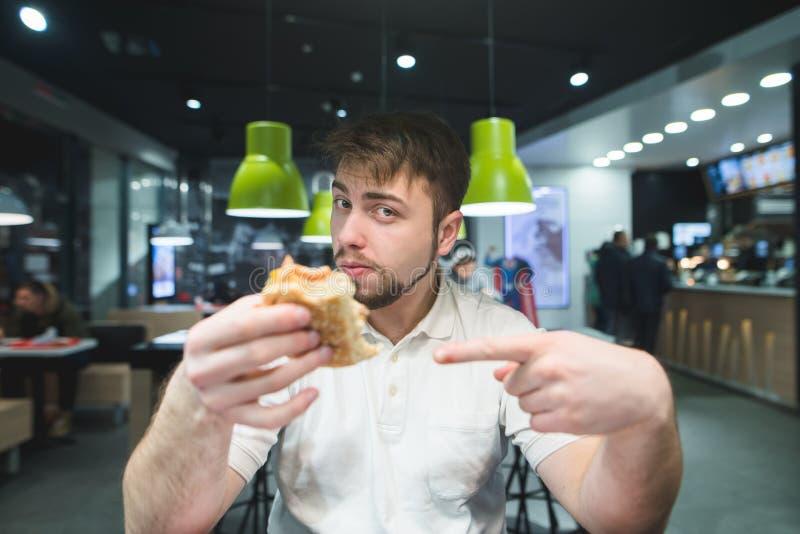 Ein gutaussehender Mann zeigt seinen Finger auf den Burger in seiner Hand und betrachtet die Kamera Der Mann isst Schnellimbiß stockfotografie