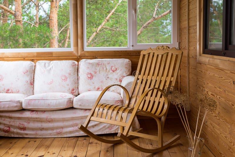 Ein hölzerner Schaukelstuhl und ein Sofa auf dem Portal oder Terrasse mit Blick auf den Wald stockfoto