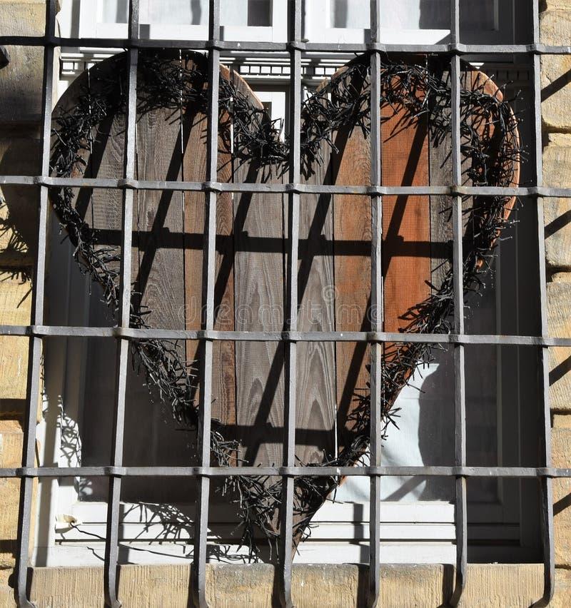 Ein hölzernes Herz hinter Gittern stockbild