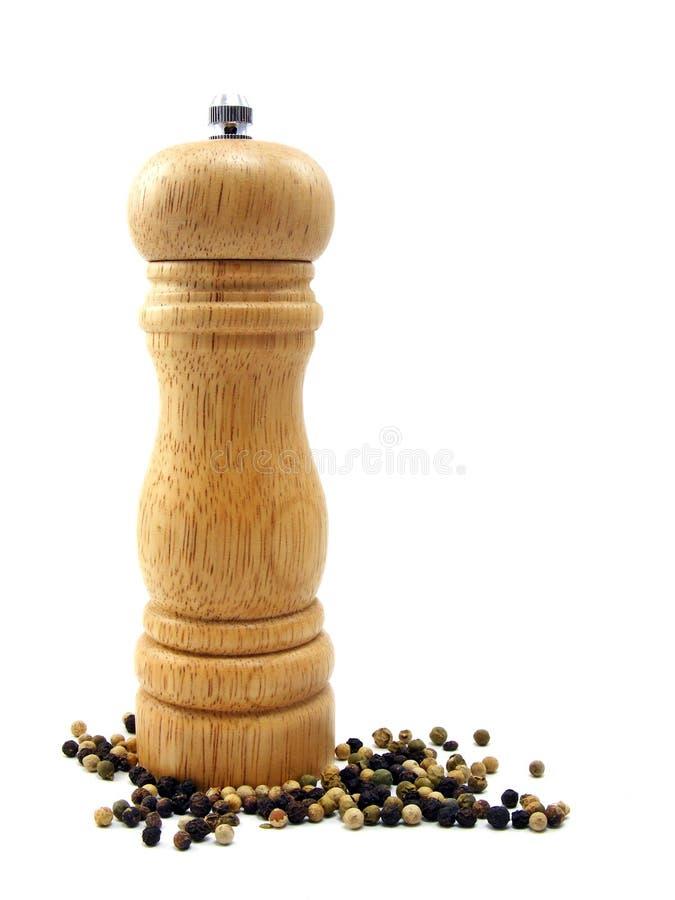 Ein hölzernes peppermill mit Pfefferkörnern stockbild