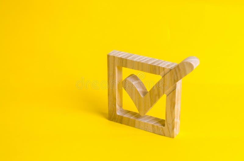 Ein hölzernes Prüfzeichen im Kasten auf einem gelben Hintergrund Das Konzept des Stimmrechts, wählend in den Wahlen Wahl des Präs lizenzfreies stockbild