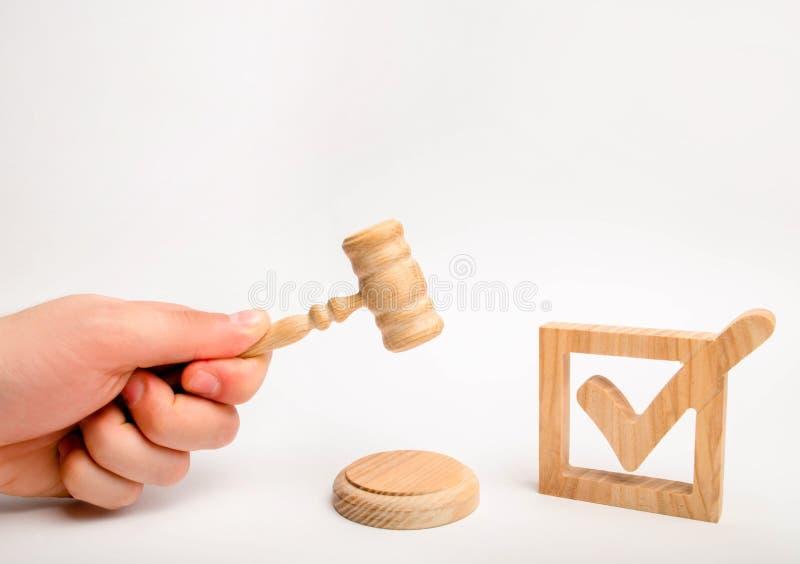 Ein hölzernes Prüfzeichen und ein Hammer des Richters auf einem weißen Hintergrund Ernennung eines Richters, Wahl zu einem Bundes stockfotografie