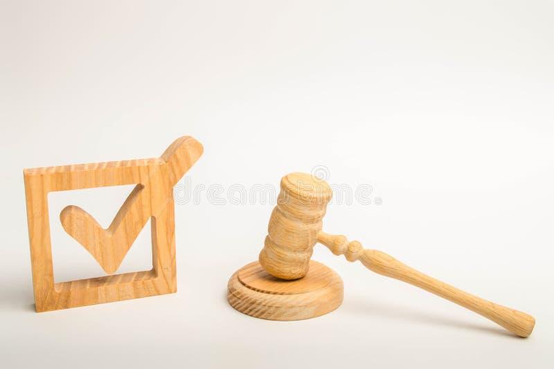 Ein hölzernes Prüfzeichen und ein Hammer des Richters auf einem weißen Hintergrund Referendum und Wahlen Ernennung eines Richters stockfoto