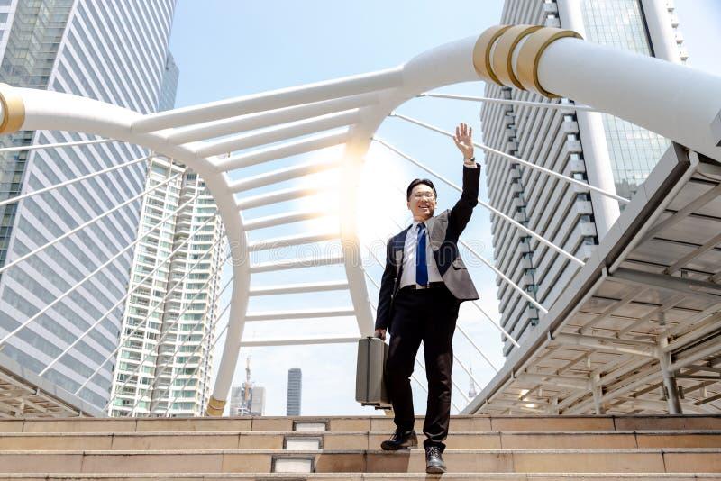 Ein hübscher Geschäftsmann ist grüßend oder sein Freund Guten Tag sagend oder stockfotografie