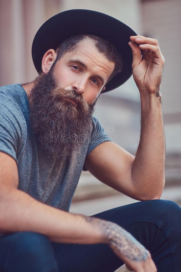 Ein hübscher Hippie-Mann mit einem stilvollen Bart mit einer Tätowierung auf hallo stockfotos