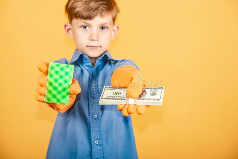 Ein hübscher Junge in einem blauen Hemd und in waschenden Handschuhen hält einen Satz Dollar in einer Hand und in einem waschende stockfoto