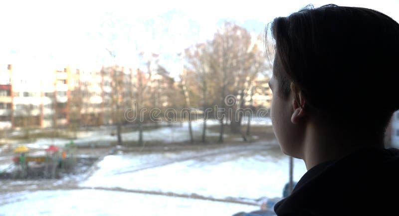 Ein hübscher Junge ein Jugendlicher schaut heraus das Fenster zur Straße stockfoto