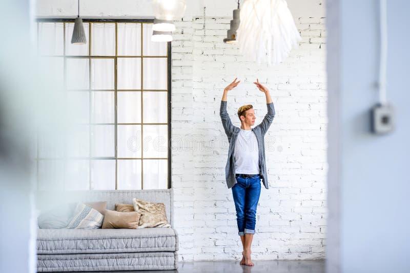 Ein hübscher junger männlicher Balletttänzer, der in einer Dachbodenart A übt stockbild