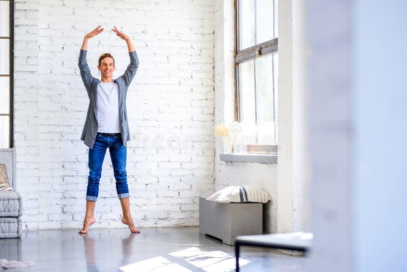 Ein hübscher junger männlicher Balletttänzer, der in einer Dachbodenart A übt lizenzfreie stockfotos