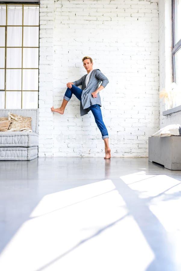 Ein hübscher junger männlicher Balletttänzer, der in einer Dachbodenart A übt stockfoto