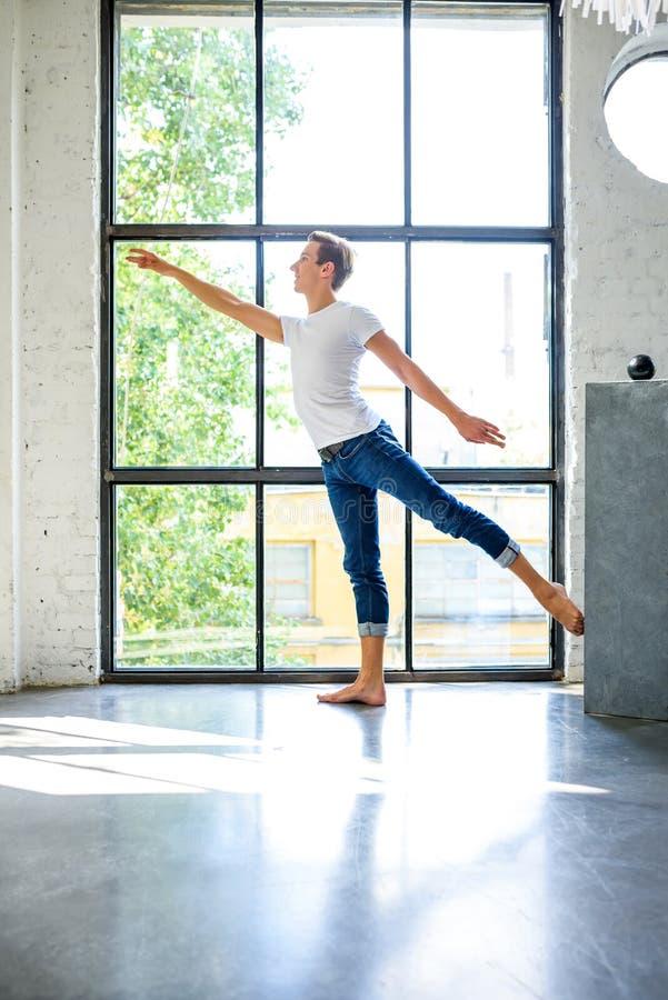 Ein hübscher junger männlicher Balletttänzer, der in einer Dachbodenart A übt lizenzfreie stockbilder