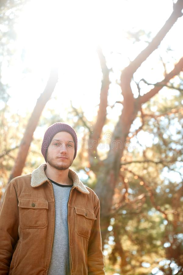 Ein hübscher junger Mann, der in den Herbstwald geht lizenzfreie stockbilder
