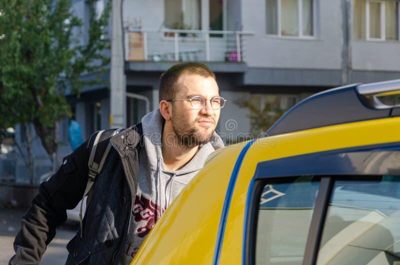Ein hübscher junger Mann, der herein an ein Taxi gelangt lizenzfreie stockbilder
