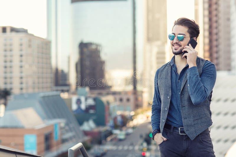 Ein hübscher junger Mann, der am Telefon in im Stadtzentrum gelegenem Los Angele spricht stockbilder