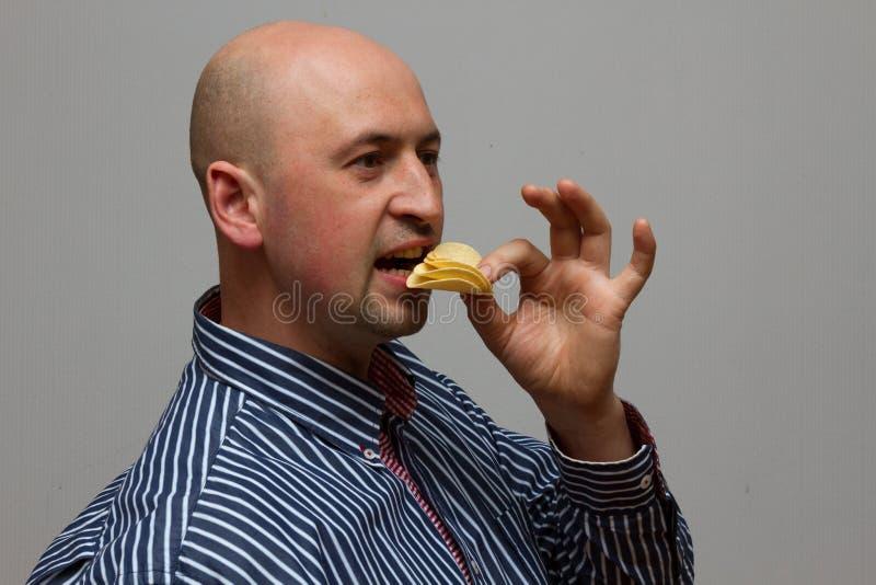 Ein hübscher junger Mann in einer Strickjacke Chips essend stockfotos