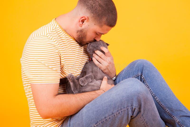 Ein hübscher junger Mann küsst und zeigt seiner Katze Zuneigung lizenzfreies stockfoto