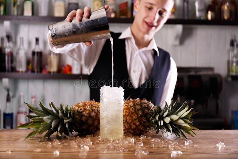 Ein hübscher Kellner und ein Pina Colada-coctail stockfotografie