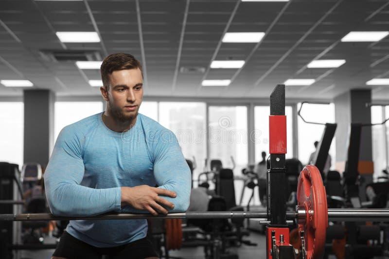 Ein hübscher männlicher Bodybuilder steht still, nachdem er in der Turnhalle trainiert hat stockbild