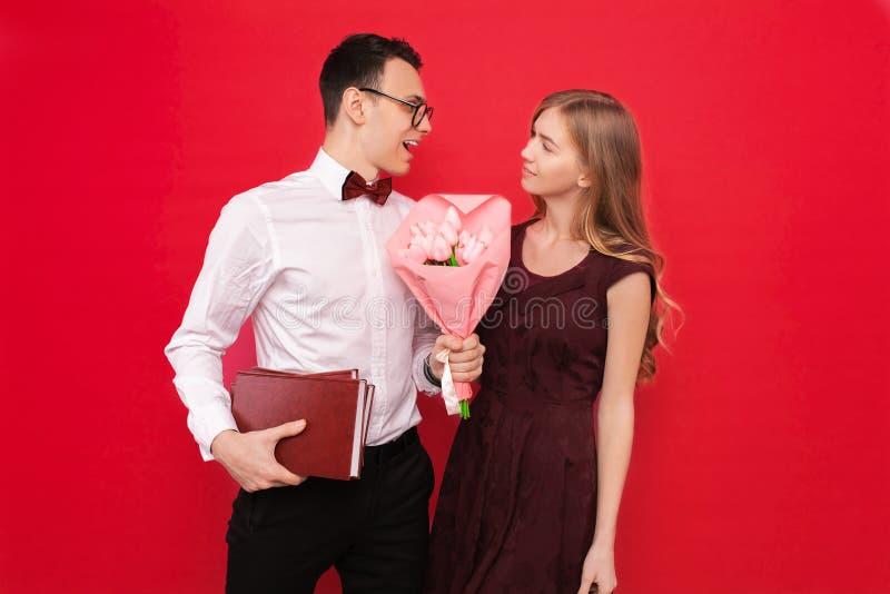 Ein hübscher Student, tragende Gläser, gibt seiner Freundin ein Geschenk und einen Blumenstrauß von Blumen gegen einen roten Hint lizenzfreie stockfotos