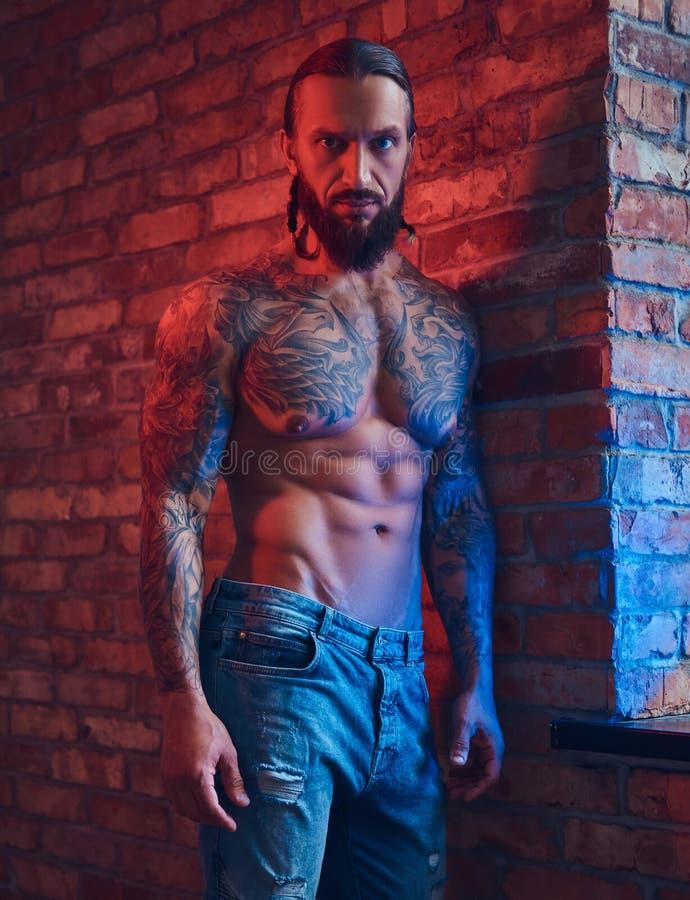 Ein hübscher tattoed hemdloser Mann mit einem stilvollen Haarschnitt und einem Bart, stehend gegen eine Backsteinmauer in einem R stockfotografie