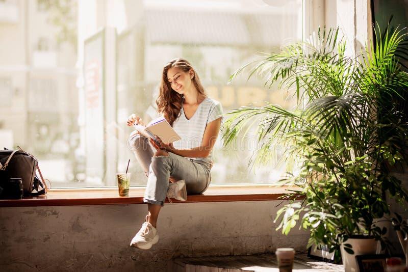 Ein hübsches dünnes junges Mädchen mit dem langen Haar, tragende zufällige Ausstattung, sitzen auf dem Fensterbrett und lesen ein stockbilder