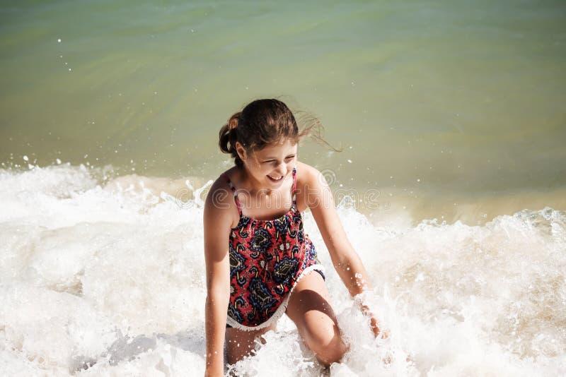 Ein hübsches Mädchen, das in den Wellen auf dem Strand, Weichzeichnung, Strandkonzept spielt lizenzfreie stockfotografie
