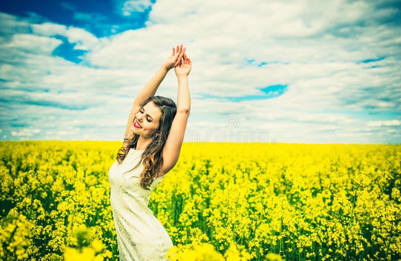 Ein hübsches Mädchen walkin auf dem gelben Gebiet mit blauem Himmel lizenzfreie stockbilder