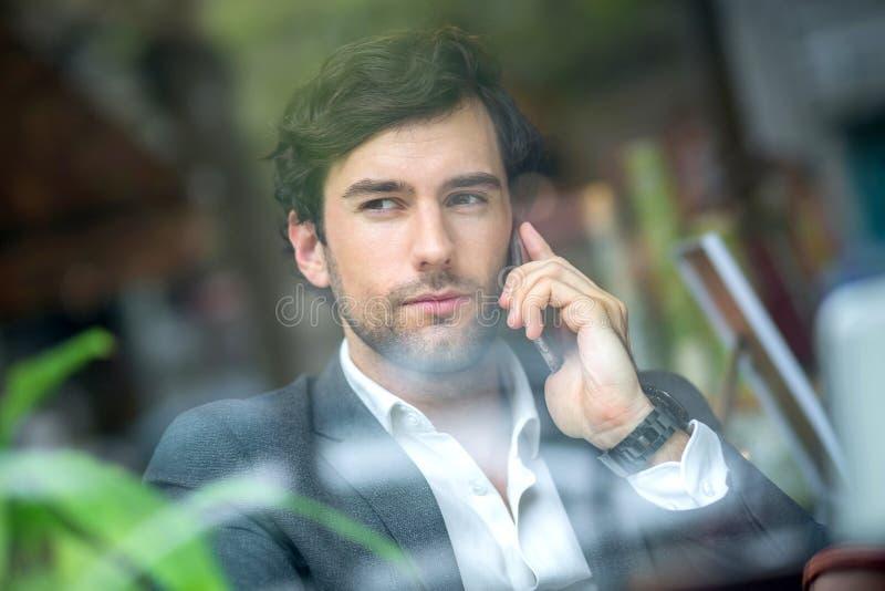 Ein h?bscher junger Mann im Fenster stockfotografie