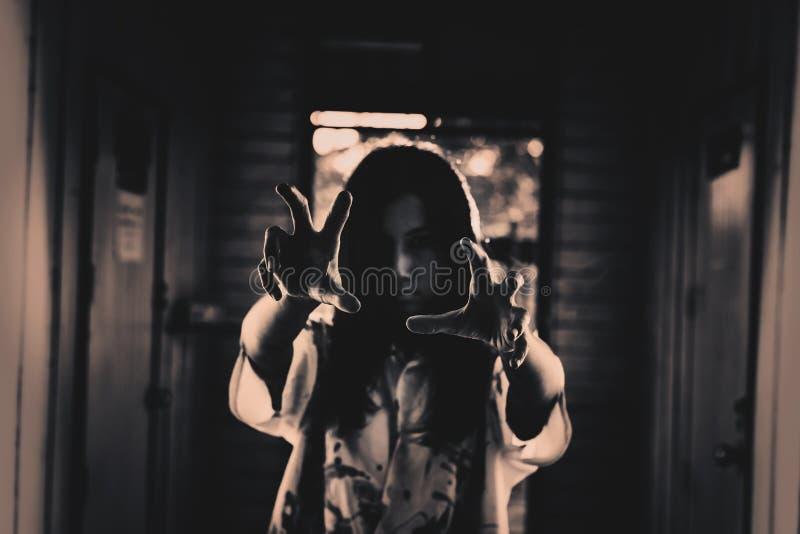 Ein Halloween-Mädchen mit der furchtsamen Hand in verlassenem Haus stockfotografie