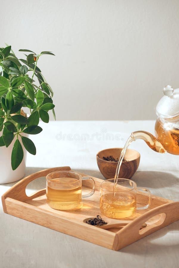 Ein Handauslaufender Tee von der Glasteekanne auf h?lzernem dienendem Beh?lter stockfotos