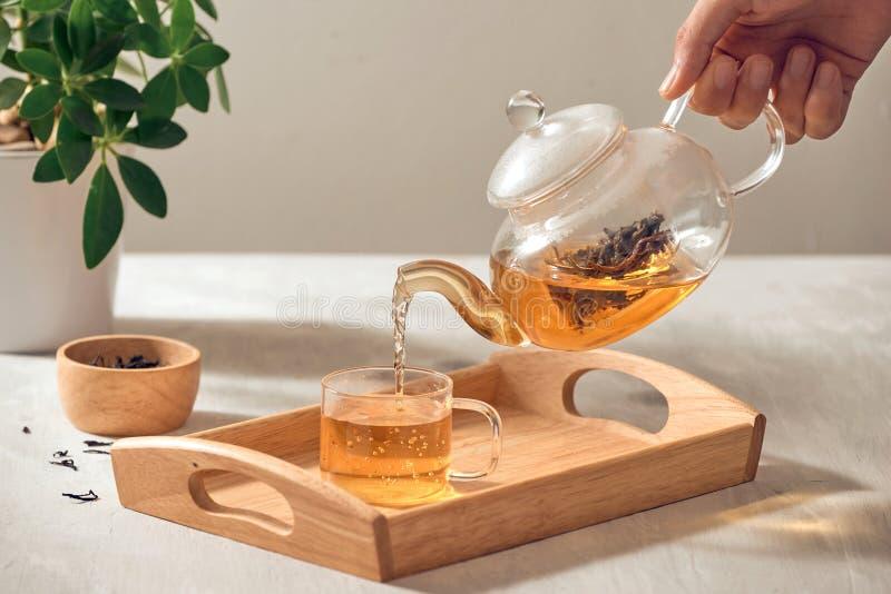 Ein Handauslaufender Tee von der Glasteekanne auf h?lzernem dienendem Beh?lter stockfotografie