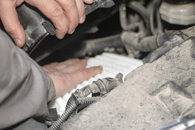 Ein Handtechniker, der die Maschine eines modernen Autos überprüft oder repariert Ersatz des Luftfilters lizenzfreies stockfoto