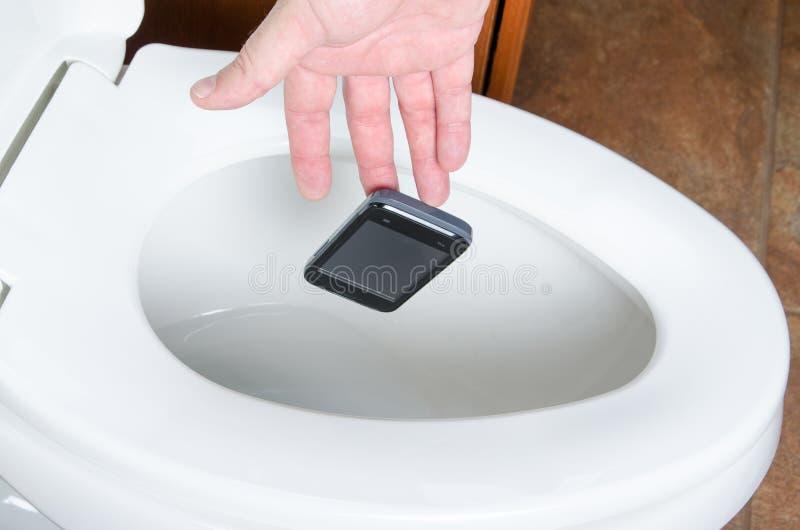 Ein Handy fallen gelassen in das Toliet lizenzfreie stockfotos