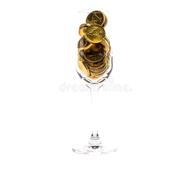 ein Haufen von Goldmünzen in einem hohen Glas lizenzfreie stockbilder