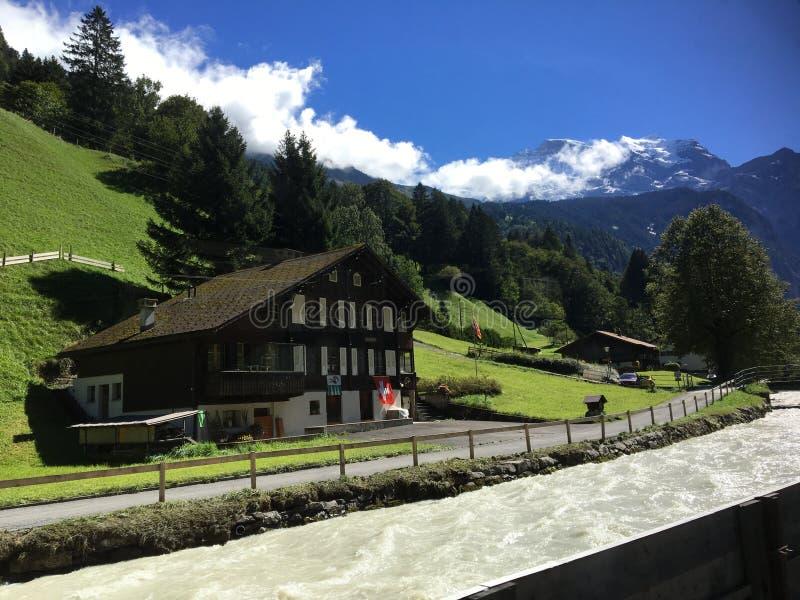 Ein Haus durch den See umgeben durch Schweizer Alpen lizenzfreie stockbilder