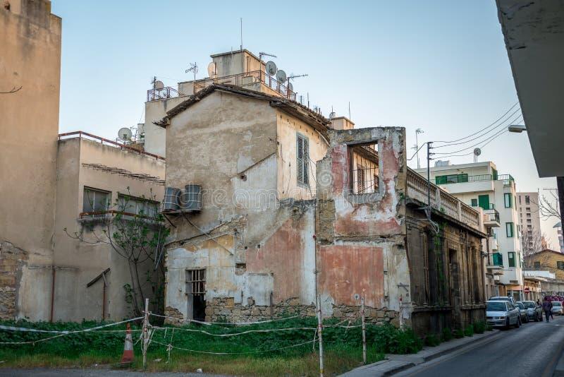Ein Haus mit defekten Wänden und Außenseite wässern Fässer für Wasserversorgung in Nikosia lizenzfreies stockbild