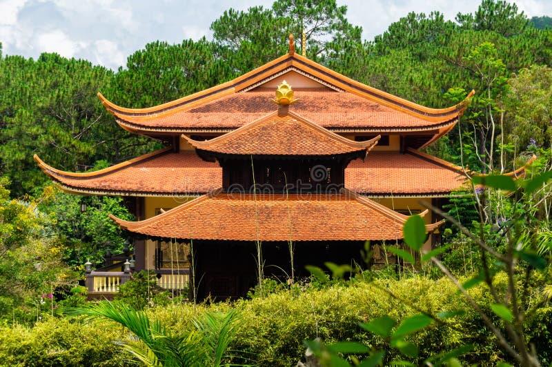 Ein Haus mit einem chinesisch-ähnlichen mit Ziegeln gedeckten Dach im tropischen Wald stockfoto