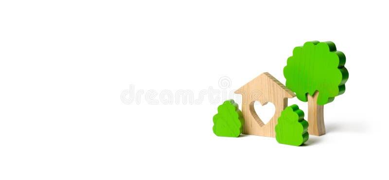 Ein Haus mit einem Herzen und hölzernen Zahlen von Bäumen mit Büschen auf einem lokalisierten Hintergrund lieben Sie Nest Erwerb  stockfotografie