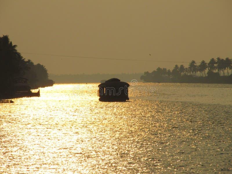 Ein Hausbootsegeln während des Sonnenuntergangs an Alleppy-Stauwassern, Kerala, Indien stockfotos