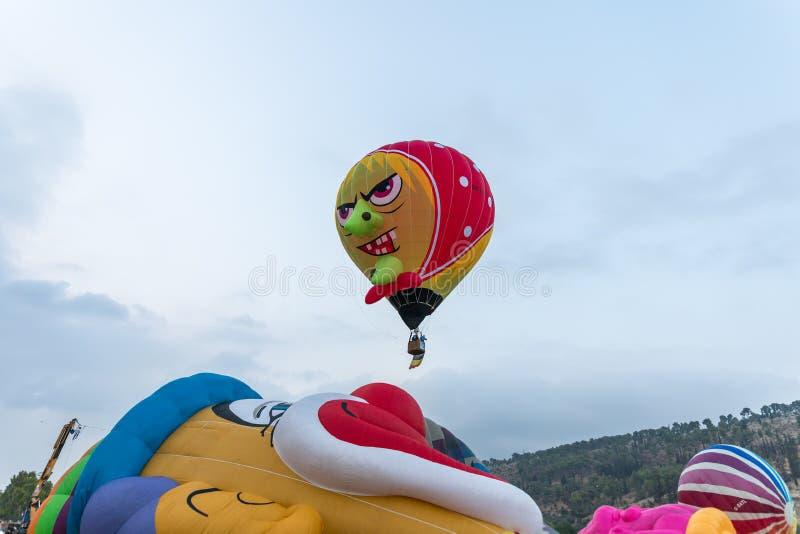 Ein Heißluftballon in Form einer verärgerten Großmutter fliegt oben am Heißluftballonfestival stockfotografie