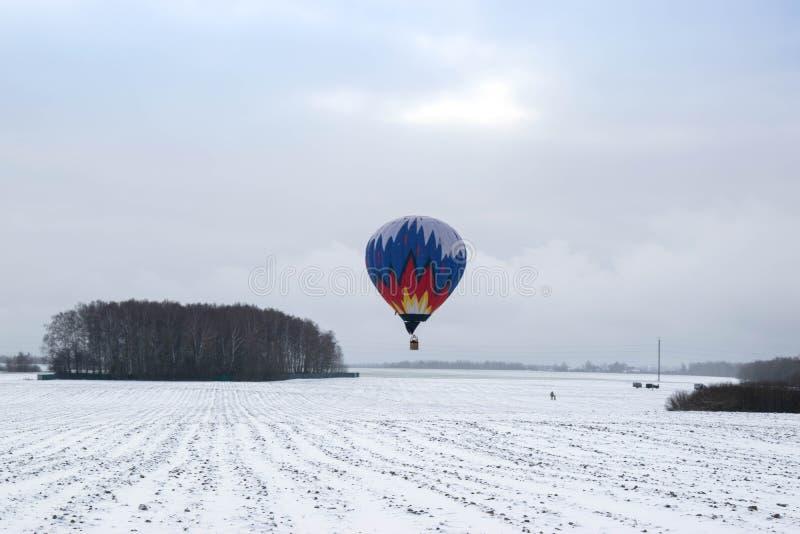 Ein Heißluftballon im Winterhimmel lizenzfreie stockfotos