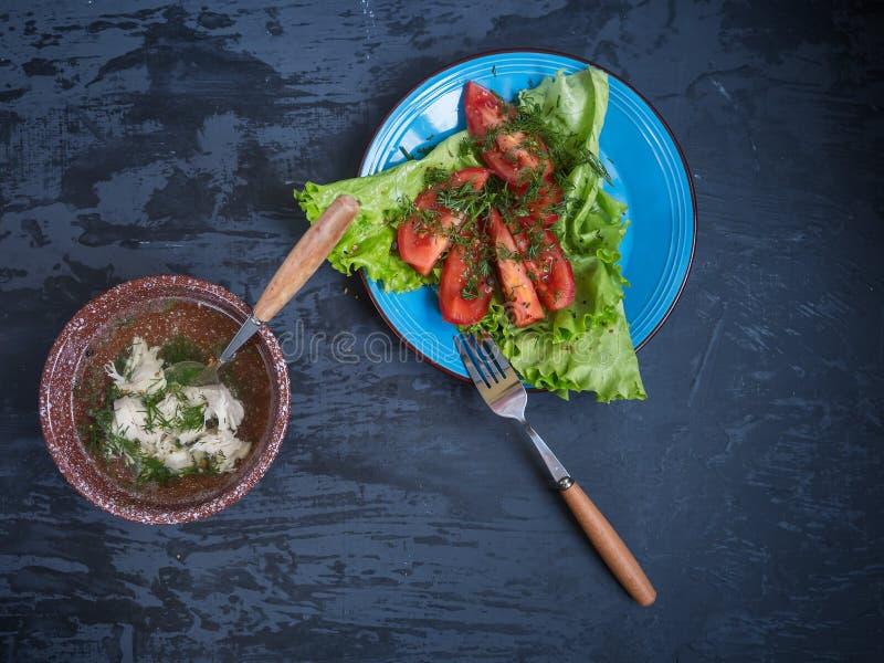 Ein helles Mittagessen von Suppenstücken Geflügelsalat von und von gehackten roten Tomaten lizenzfreies stockfoto